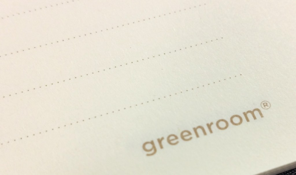 A close-up shot of the dotted ruling and logo printed onto each page of the Greenroom Recycled Notebook