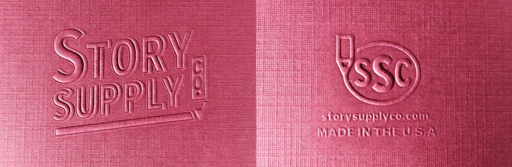 An image showing the embossed logos on the front (left) and rear (right) covers of the Story Supply Co. Pocket Staple Edition 407 Notebook