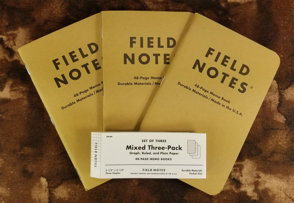 Mixed three-pack of Field Notes Kraft notebooks, fanned out, with the belly band on top.