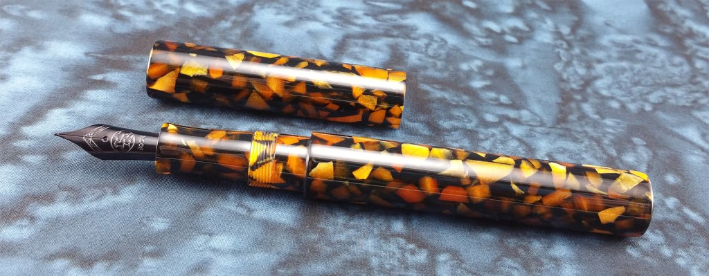 A picture of the Newton Pens Eastman Fountain Pen in orange flake acrylic, uncapped, with the pen and cap laying side-by-side