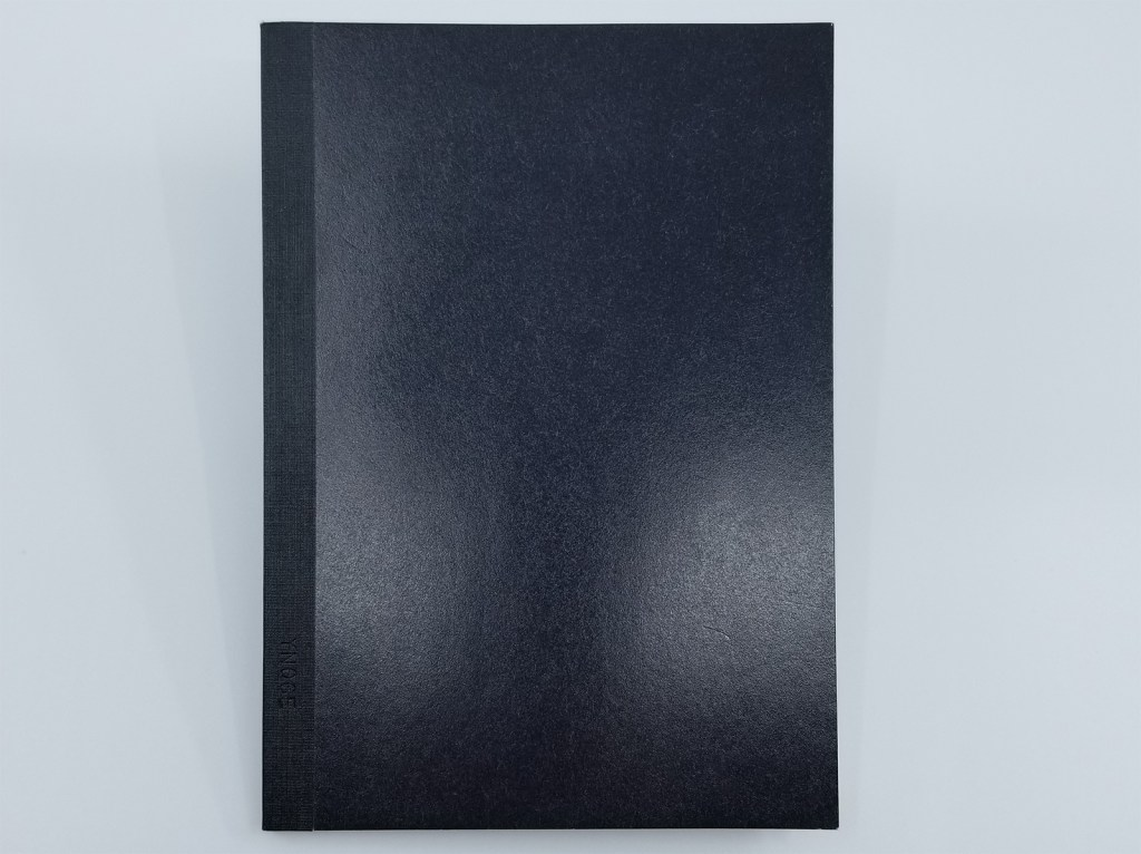 A photo of the Kokuyo Systemic A6 Notebook Refill front cover, in black
