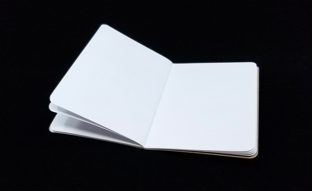 A Scout Books pocket notebook, open, showing how it lays flat (mostly)