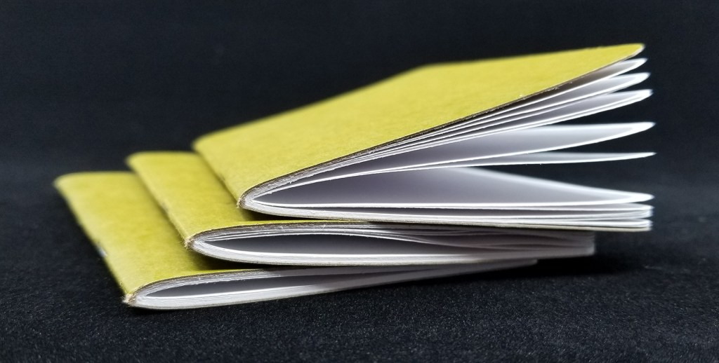 A stack of Scout Books Pocket Notebooks showing the paper edges and folds