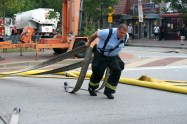 A Baltimore firefighter pulls a hose through the street in Fells Point. (Photo/Kendra Yost)