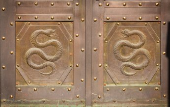 Metal door with opposing snakes