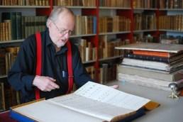 """Ove Hagelin förevisar en av Hagströmerbibliotekets rariteter, den första utgåvan av Carl von Linnés """"Systema Naturae"""" från 1735."""
