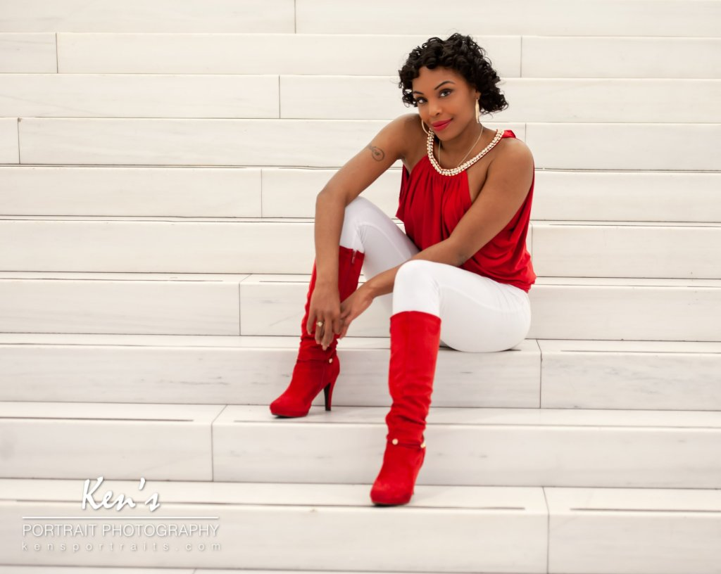 Setting the Trend by Kens Portrait Photography. Maribel sits on the steps in the Oculus located in New York City. Her red shirt and red boots contrast perfectly with the white marble steps. It is no wonder that the Fashion Tag Blog considers red boots to be one of the hottest fashion trends of 2018.  The Fashion Portrait Experience at Ken's Portrait Photography includes an initial consultation, two hours of in studio or on-location photography, and a personalized image review session. You can fulfill your fashion dreams by adding professional hair and makeup artistry to the fashion portrait experience.  The studio for Ken's Portrait Photography is located right on the southwest corner of West Capital Park in Albany, NY. In addition to what can be created in the studio, this historic and architecturally rich area provides beautiful backdrops for professional portraits, couple portraits, senior portraits, family portraits, engagement portraits, and wedding portraits.