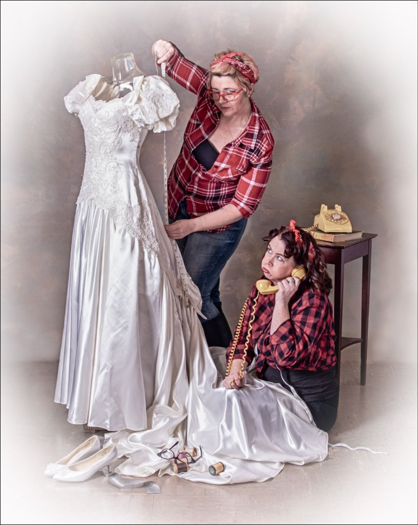 Stressed out Seamstresses by Kens Portrait Photography. A wonderfully playful image from a recent photo shoot with Lori and Jill. The inspiration for this image stated with the wedding dress that appears in the recent Said Yes to the Dress post.  The image needed something more, some kind of action, something to complete the story in the photo. Lori and Jill made the perfect addition to this image as a pair of retro-looking seamstresses working late into the night to make the final preparations on the wedding dress for the next day.  One of the image themes for the studio for 2019 is to create photos with a Norman Rockwell type look. This is the first in the series of Norman Rockwell type images from Ken's Portrait Photography this year.  This wedding dress is one of the wardrobe items recently acquired by the studio. The studio has an inventory of clothing available for fashion portraits and creative photo sessions.