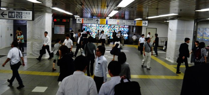 Commuters in front of the Shimbashi station stained glass peacock