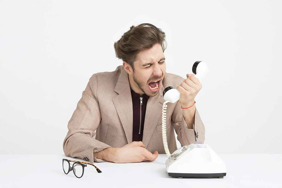 man screaming angrily over the telephone