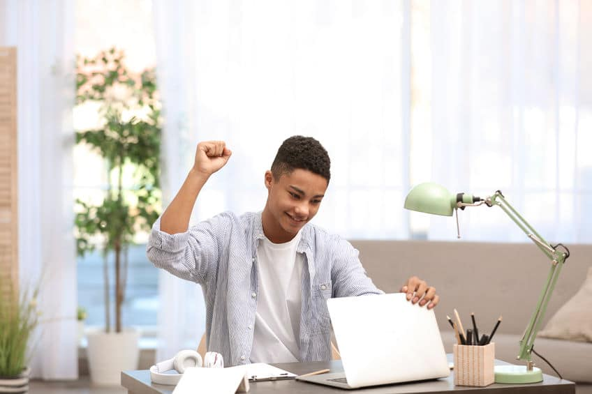 a guy holding a laptop while happily pumping his fist in the air