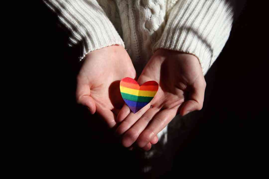 hand holding a lgbt pride heart color