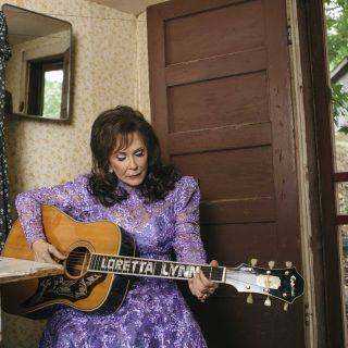 Loretta Lynn playing guitar as she celebrates 50 years since Coal Miner's Daughter song was released. Photo by David McClister.