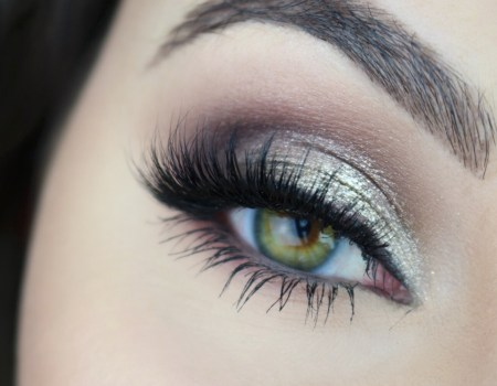 Closeup on an eye with a glittery smokey eye featuring silver glitter and deep purple eyeshadow.