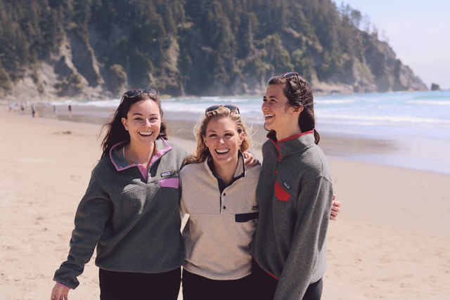 Three girls laughing while hugging at the beach
