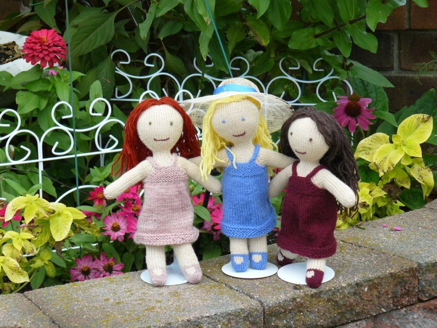 Three hand-knit dolls stand next to a small garden.