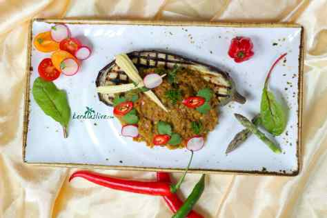 Baingan Bharta - A delicious smoky roasted eggplant cooked in onion tomato gravy with aromatic spices. When treated right, it's creamy and earthy—a standout star in your dining table.