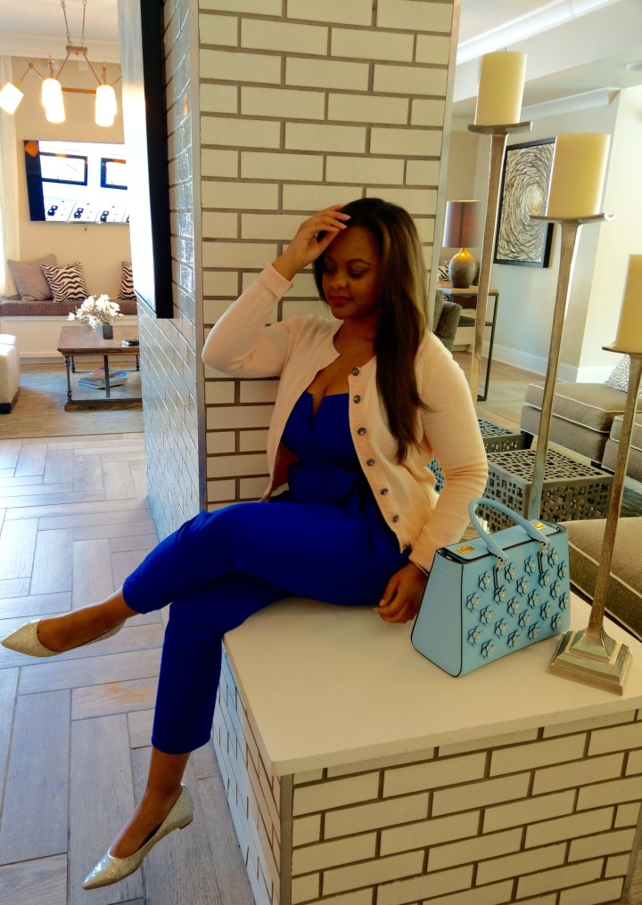 Keri Elaine is wearing a cobalt blue jumpsuit with a pastel Zara cardigan and Henri Bendel bag