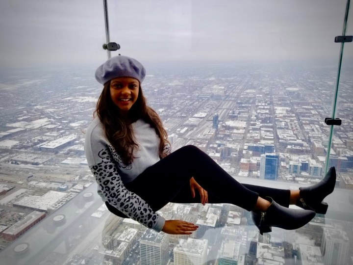 Foggy Chicago view of a beautiful young black woman in Chicago. Black chunky ankle boots and a cheetah sweatshirt.