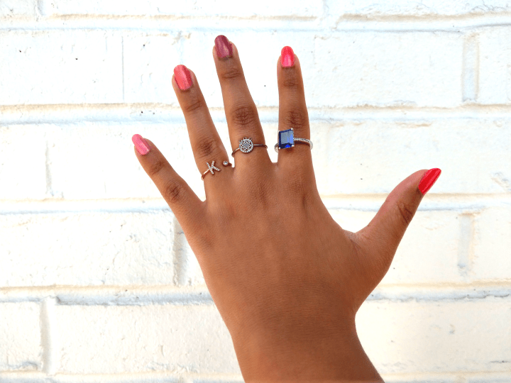 Ombre Pink manicure with k initial ring and an emerald cut sapphire