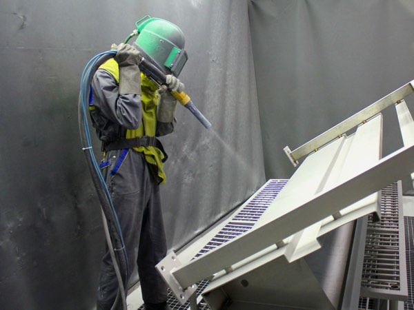 A man using sandblasting gun on metal, wearing helmet and saftey clothes.