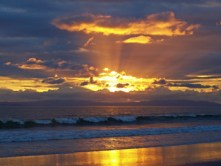 Shades of orange and yellow shine out from a setting sun whose rays radiate from the center. Green waves froth white as they roll onto Playa Zancudo, Costa Rica in the Puntarenas Province of the South Pacific Coast across from the Osa Peninsula.