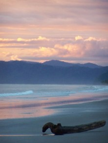 A beautiful pink glazes the beach with blue mountains, the pink reflecting in the wet sand on Playa Zancudo, Costa Rica in the Puntarenas Province of the South Pacific Coast across from the Osa Peninsula.