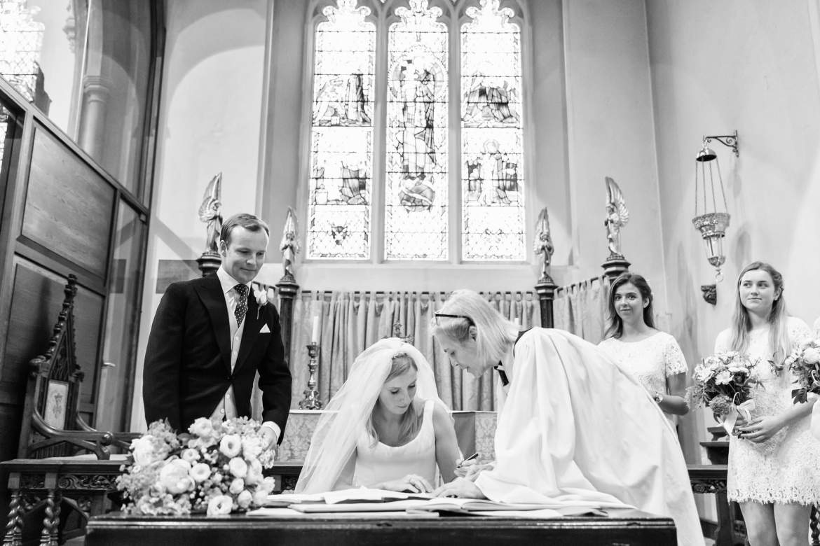 The couple sign the marriage register