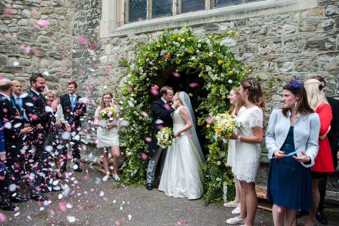 The couple kiss under the archway of the church