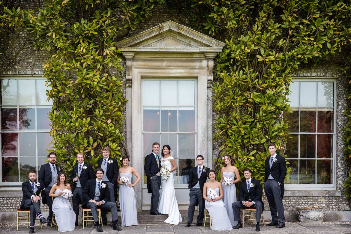 Bridesmaids, ushers and the bride and groom pose for pictures at Goodwood House