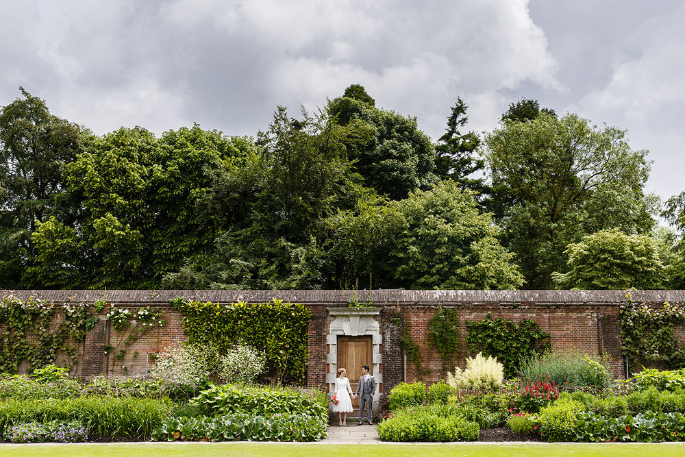 Cliveden house wedding photos bride and groom against wall