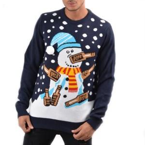Op de afbeelding is een donkerblauwe kersttrui sneeuwpop te zien met sneeuw, bier, een rood met gele sjaal en een lichtblauwe muts met witte 3D bal.