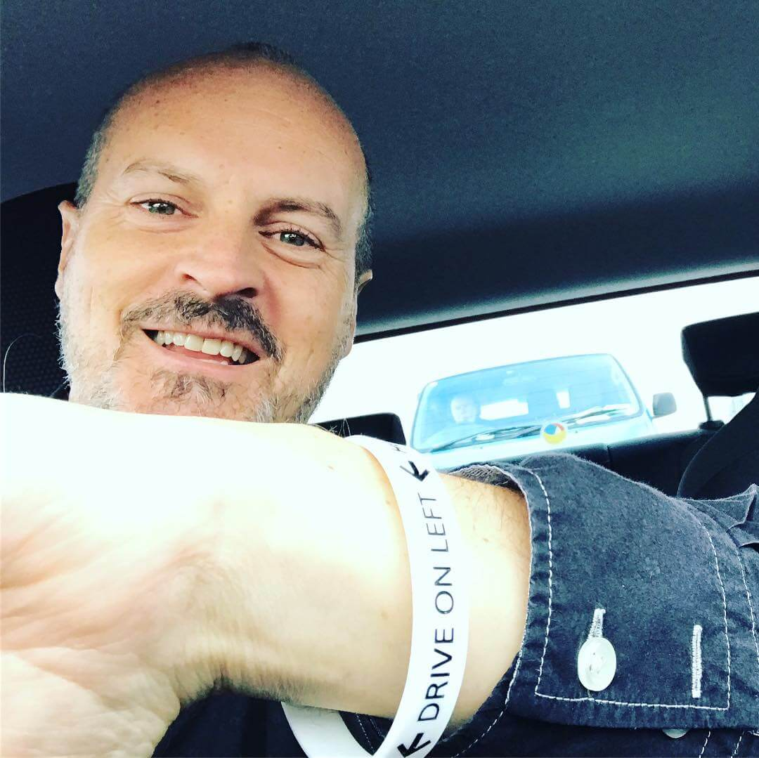 The rental car company in Dublin gave me a bracelet to remind me to drive on the left hand side of the road. I'm smiling as I snap a selfie in the rental care.