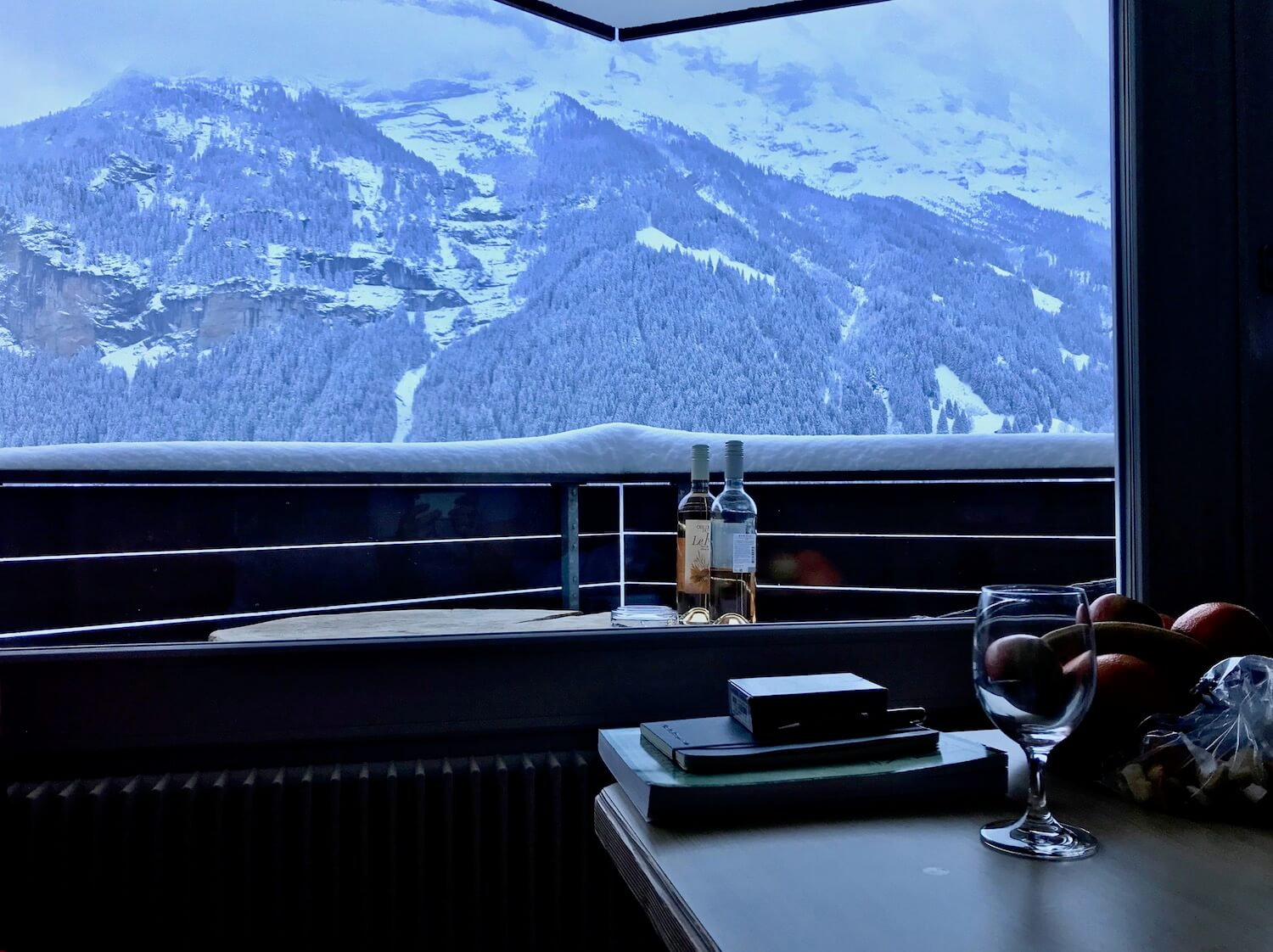 View from a hotel room at Hotel Spinne looking past a table with fruit and books to the balcony table with two bottles of wine just beneath the rail with four inches of snow. In the background is the base of Eiger (13,000ft).