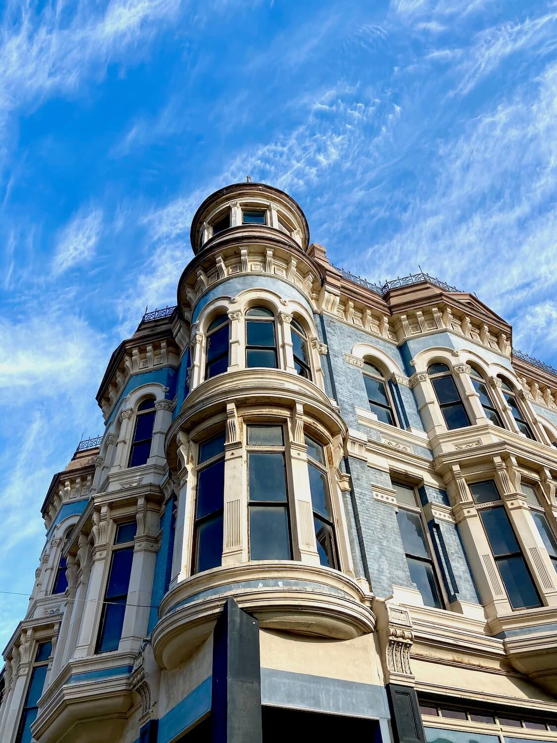 A towering Victorian building rises up on the Main Street of downtown Port Townsend. The ornate three story building utilities a combination of light blue brick with ornate white bordered windows with metal fencing like grating that lines the roof. The sky above is blue with swirls of white clouds.
