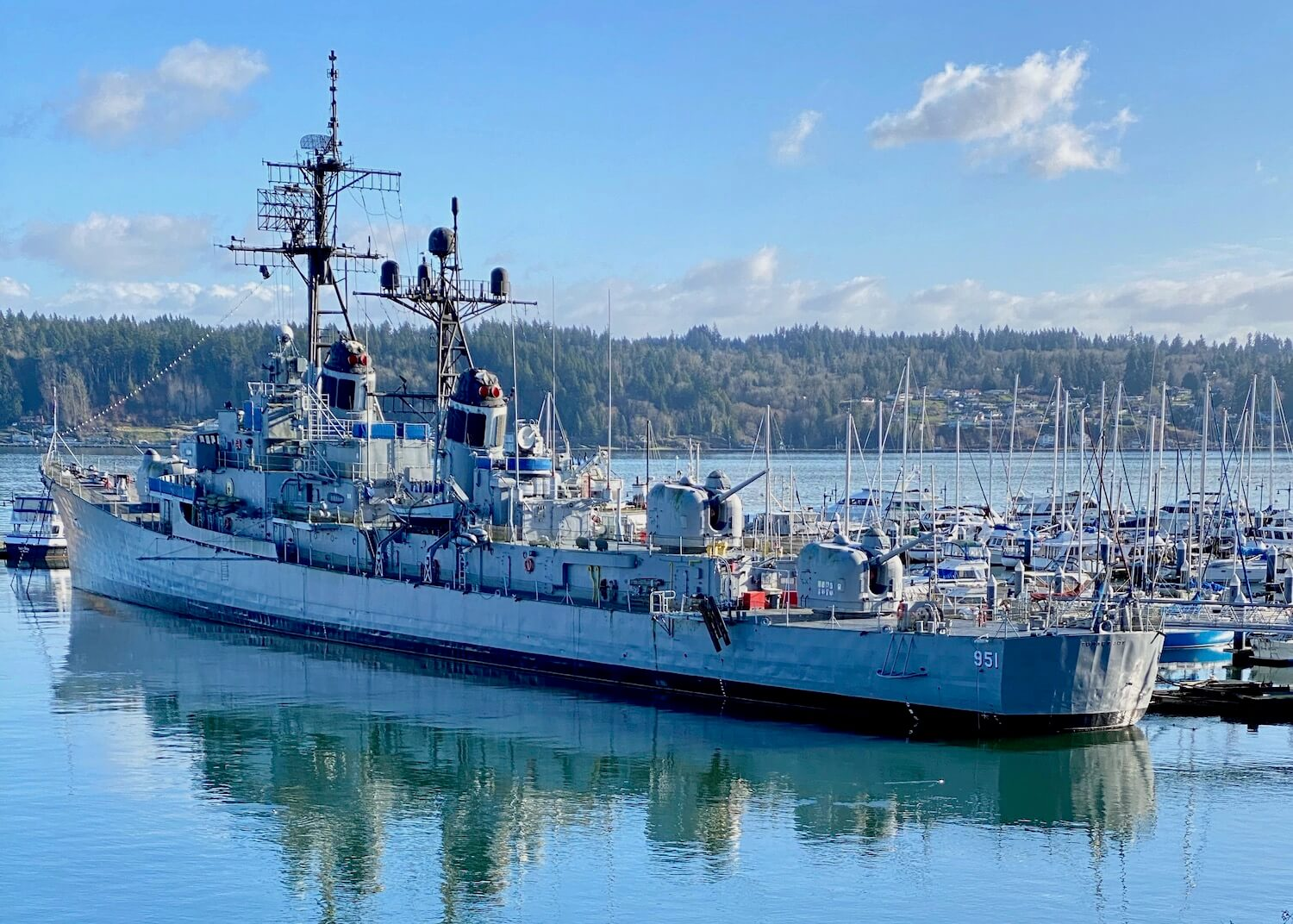 The USS Turner Joy is a floating naval museum in Bremerton Washington and this photo is of a warship painted gray with a marina of smaller, mostly sailboats in the distance.