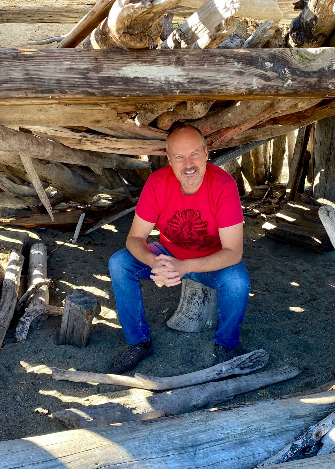 A selfie photo of Matthew Kessi on a Whidbey Island beach. He's smiling and wearing a bright red t-shirt underneath a shelter made from drift logs.