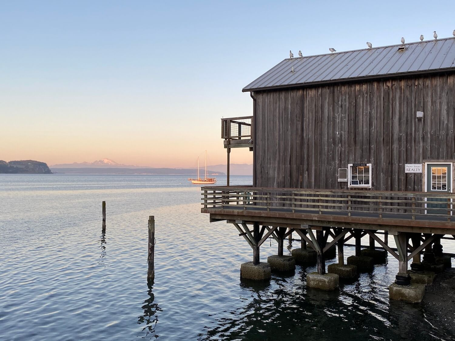 The pier at Coupeville, on Whidbey Island hovers above the Salish Sea as seagulls make their perch on the metal roof high above. The sun is setting and casting a pinkish glow onto Mt. Baker, which is in the background of the photo.