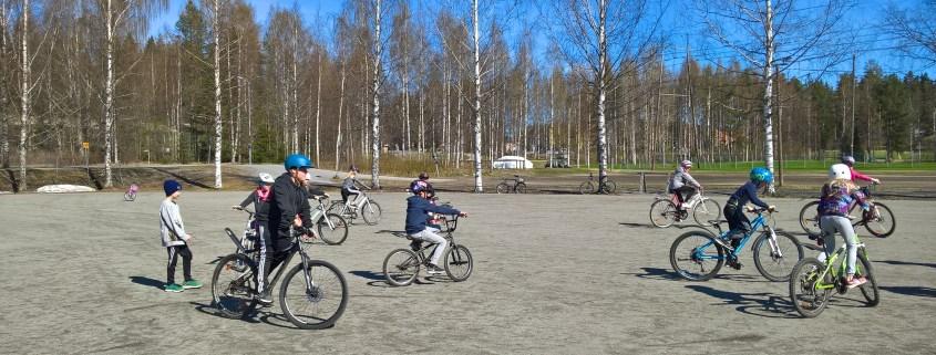Pyöräileviä lapsia hiekkakentällä, aurinkoinen kevätpäivä.