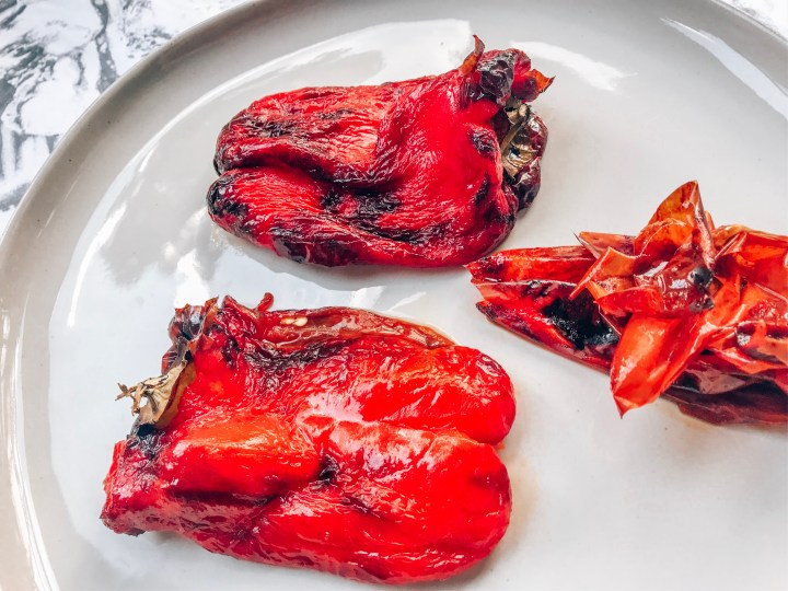 Roasted red bell peppers on a plate with peeled skins