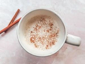 Eggnog in a mug with nutmeg and cinnamon sticks