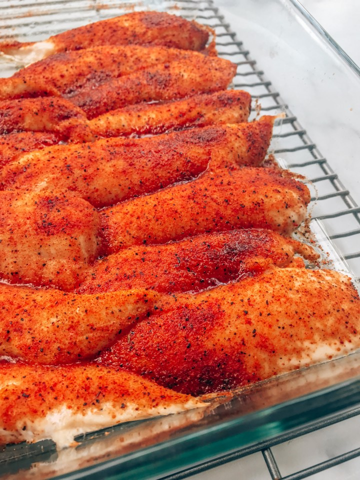 Seasoned and baked chicken tenders on a cooling rack.