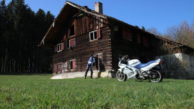 Motorrad vor dem Bauernhof, Fahrer schaut durchs Fenster