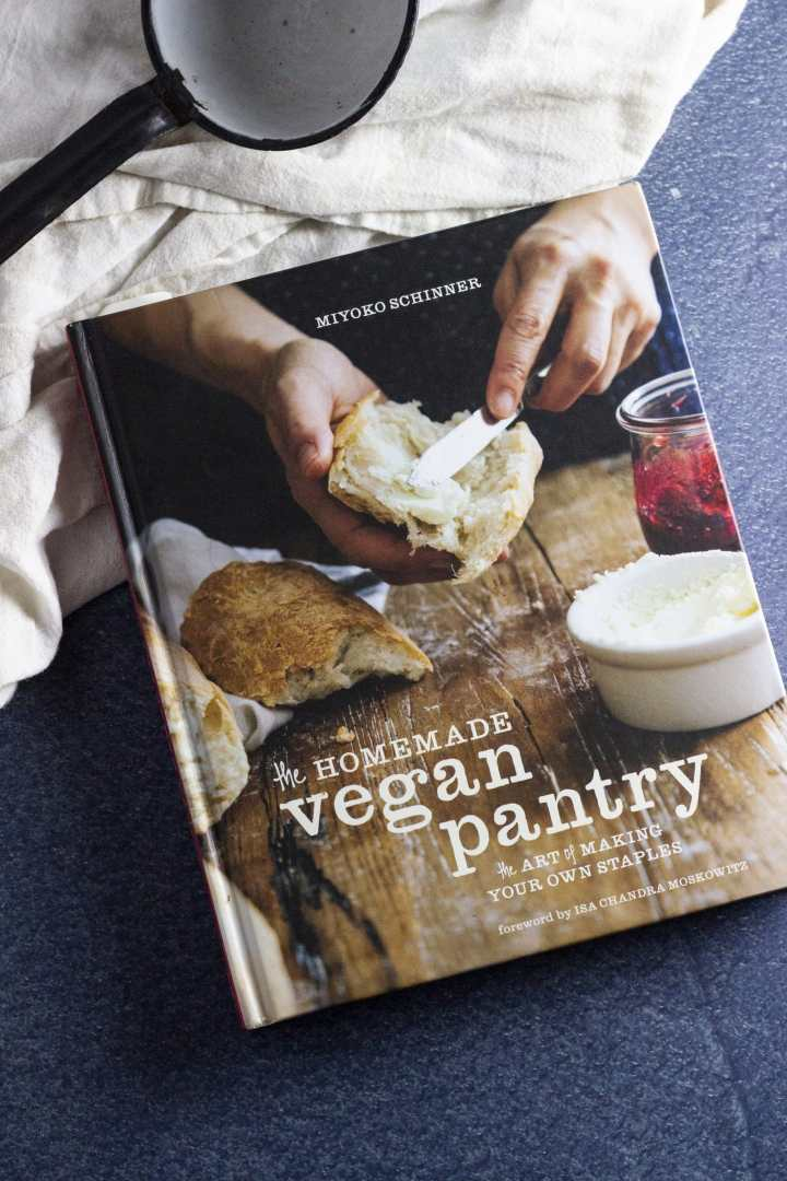 This is an image of The Homemade Vegan Pantry by Miyoko Schinner, on a blue marbled surface and a white dish towel. This book has been an absolute life saver for me.