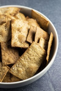 A bowl full of freshly baked, whole wheat crackers on a blue background
