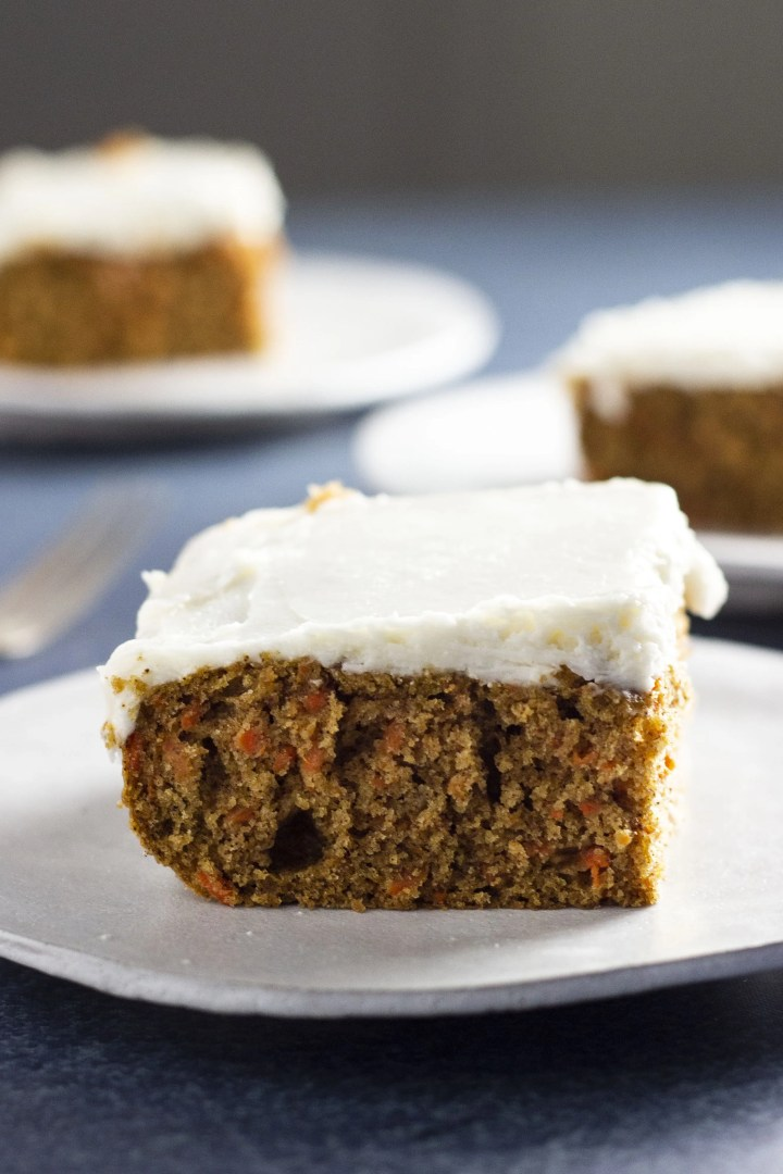 Frontal shot of a slice of delectable vegan carrot cake topped with vegan cream cheese icing.