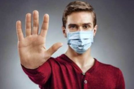 picture of person with hand stretched out and wearing a mask with red shirt