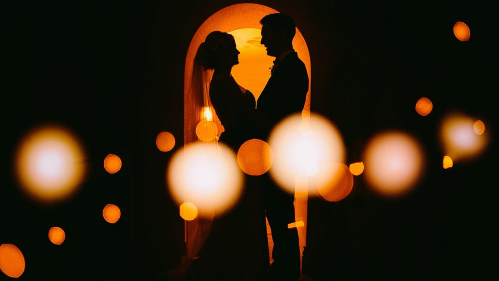 A silhouette of the Bride and Groom with lights in the foreground