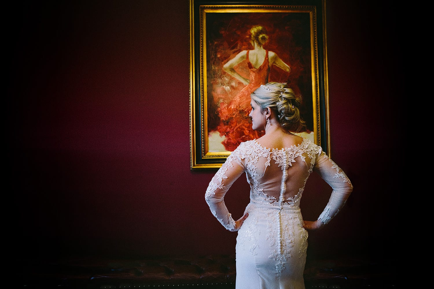 A bride poses in front of a painting