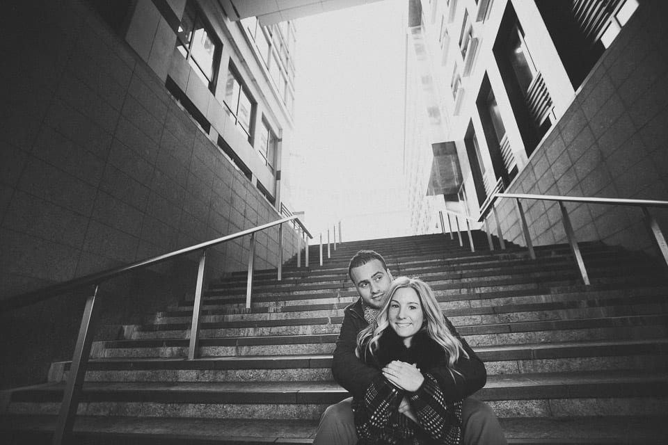 Black and white image of engaged couple sitting on the steps in Canary Wharf